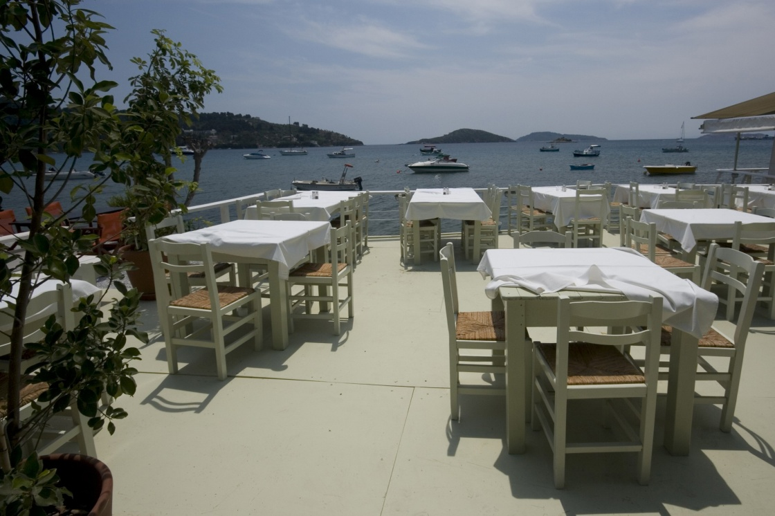 'Dining tables in local restaurant with a view of the sea Skiathos, Greece' - Skiathos